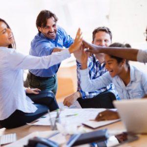 Equipe comemorando o sucesso nos negócios fruto da psicologia organizacional